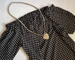 black and white off the shoulder top with a chunky silver necklace