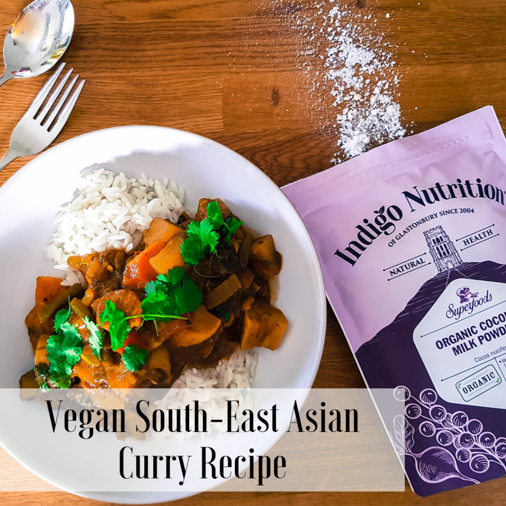 vegan curry on a wooden bench next to an indigo herbs packet