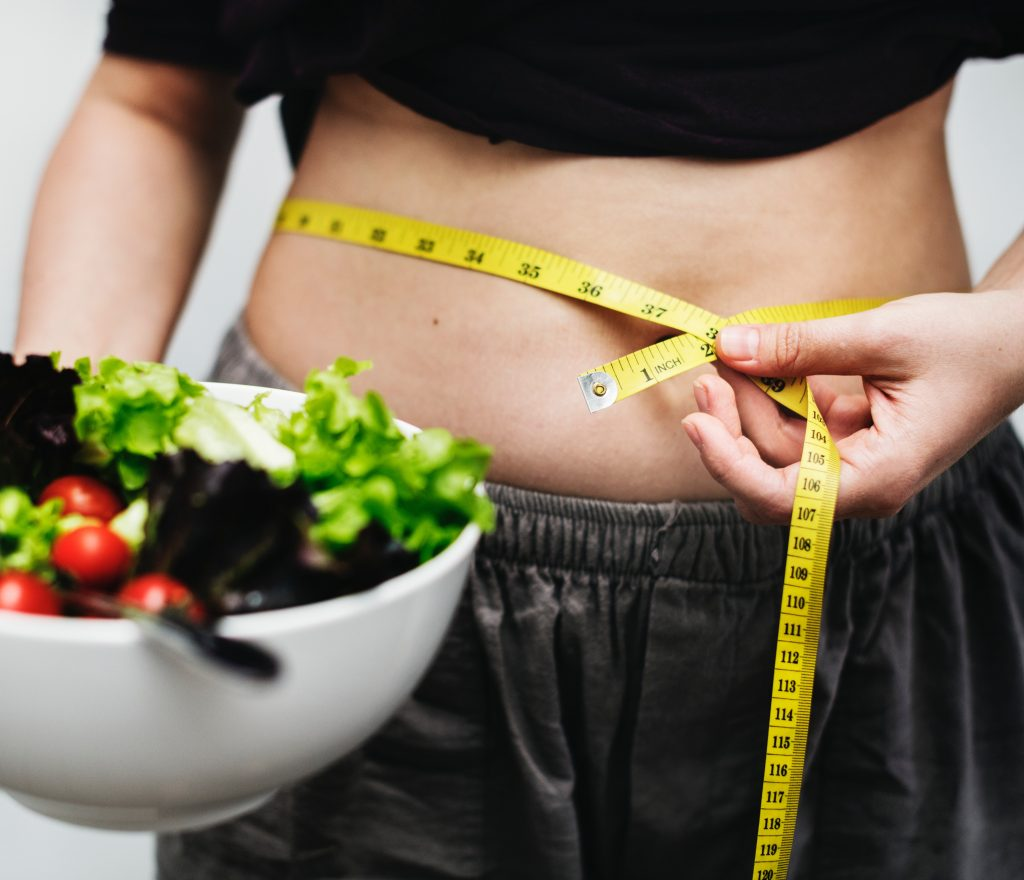 a woman measuring her stomach in front of a bowl of salad