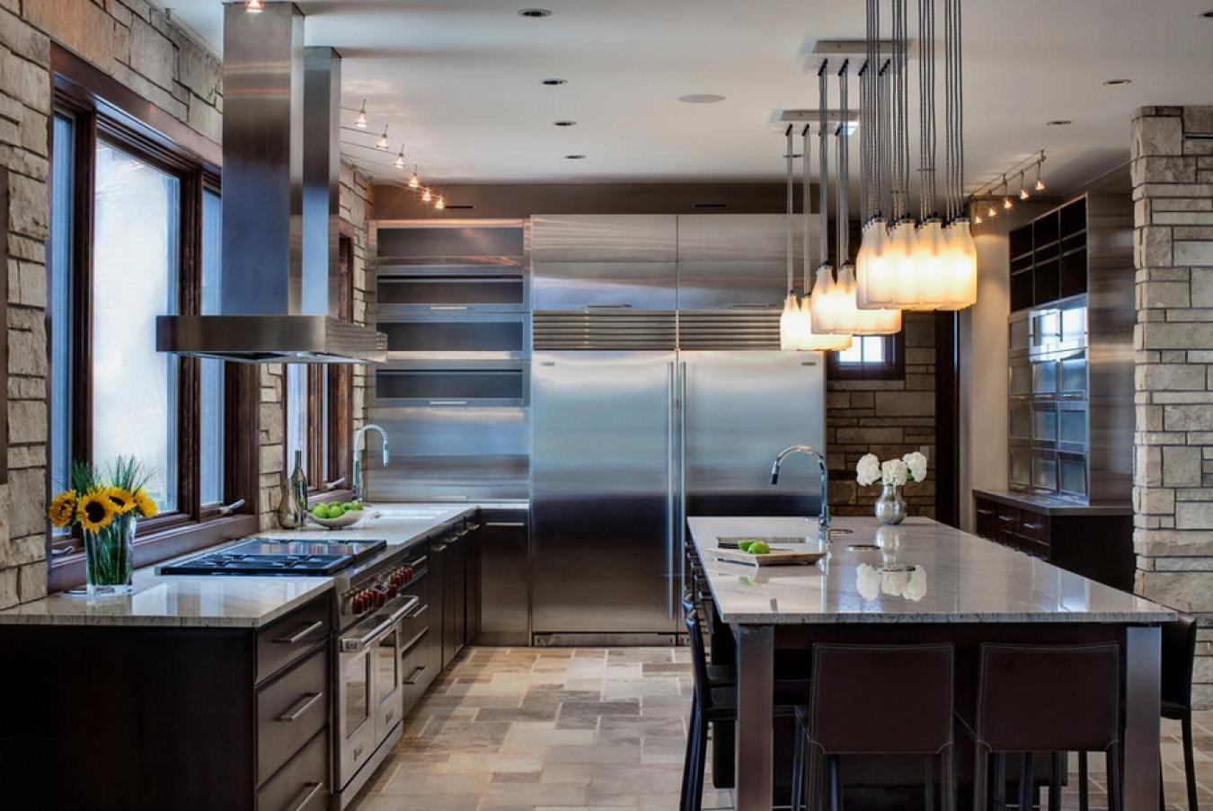 Modern-kitchen-interior-with-a-high-tech-cuisine-and-big-fridge-along-with-fine-dining-space-with-beautiful-hanging-lamps-decor