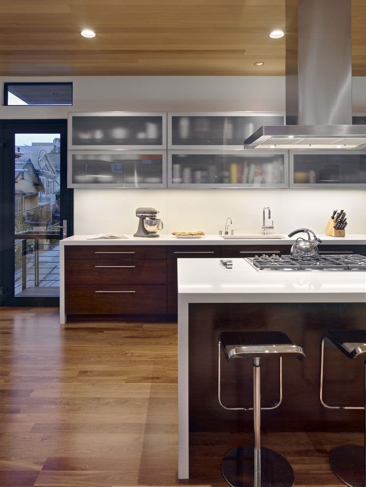 Trendy Kitchen With Glass-front Cabinets And Dark Wood Cabinets