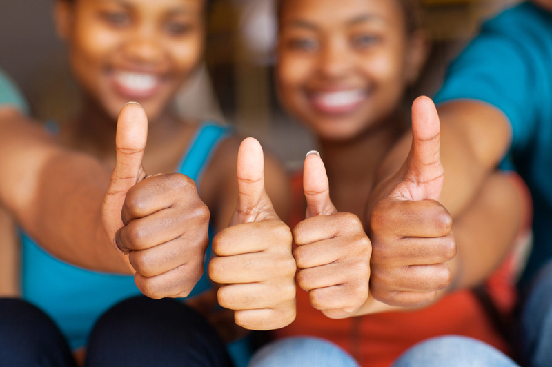 group of african friends thumbs up closeup
