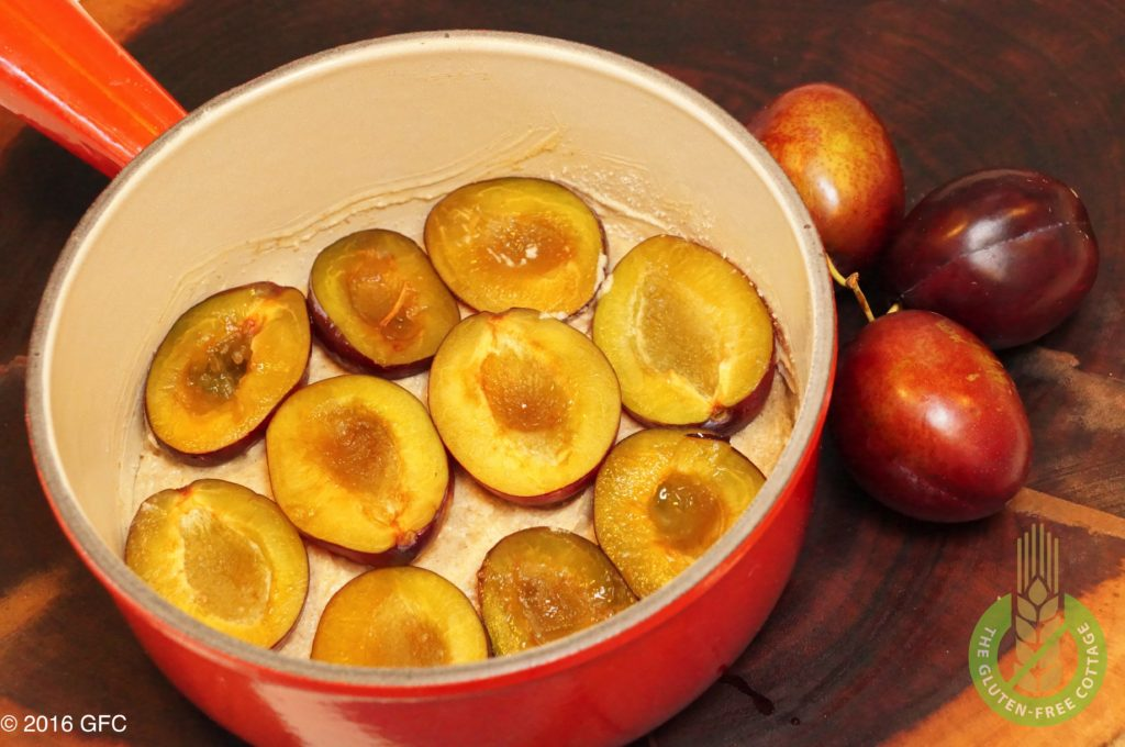 Dough with fresh plum halves as a topping (gluten-free plum cake).