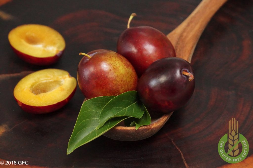 Fresh plums and plum halves (gluten-free plum cake).