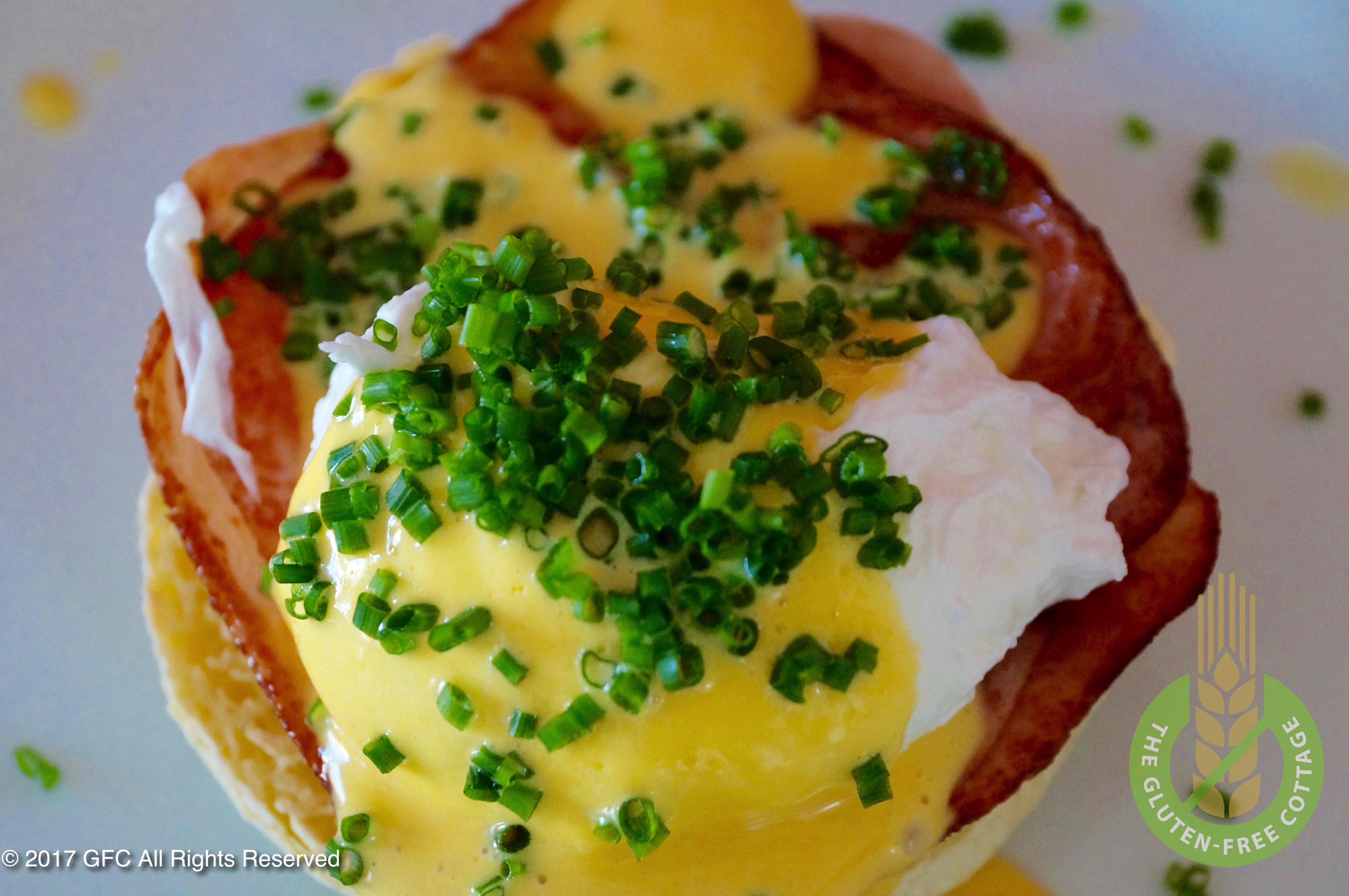 Eggs Benedict on top of gluten-free English muffins (gluten-free eggs Benedict/ gluten-free English muffins).