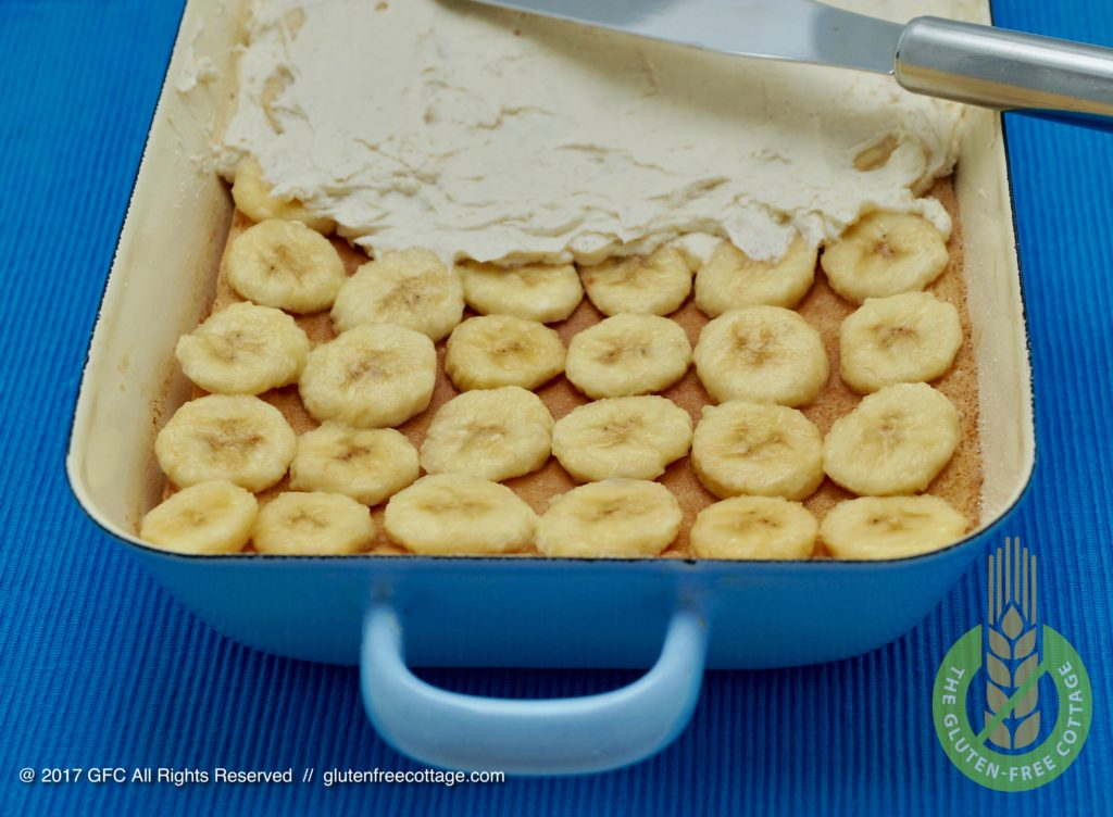 Evenly spread cream filling on top of banana slices (gluten-free banana cake with chocolate glaze).