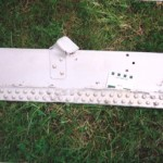 """Detail of the large aluminium spar showing remnants of plate held by a double row of aluminium rivets, also some """"L"""" brackets also riveted on. Scale in cm and inches."""