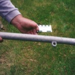 An aluminium stanchion 60cm long and 3.7 cm wide. An aluminium eye with 1.7cm internal diameter is welded to it. It has an inner post for extension with a screw threaded top. Scale in cm and inches.
