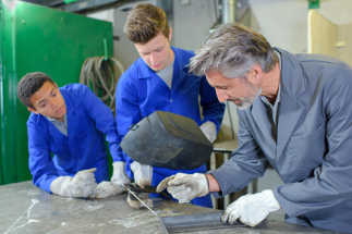Man coaching two younger men in engineering workplace
