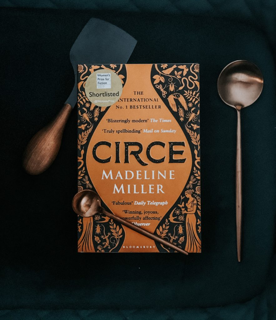 Madeline Miller's Circe book on dark green background with copper cutlery