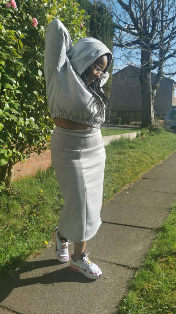 Image of woman in cropped hooded top and matching skirt