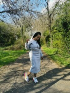 Black woman wearing grey cropped hoodie and midi length pencil skirt
