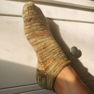 Mindful knitting - A foot wearing a short hand knitted sock