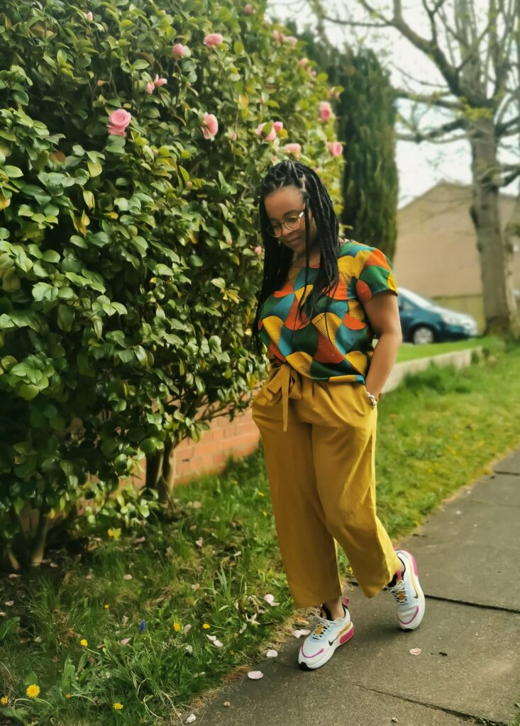 Black woman with braids stands outdoors wearing a colourful Scout Tee and handmade trousers. She is looking down towards the ground and is in mid stride