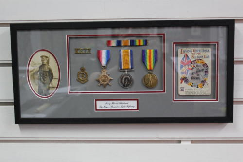 Trio of WW2 Medals with badges, phots and a postcard sent home from the front.