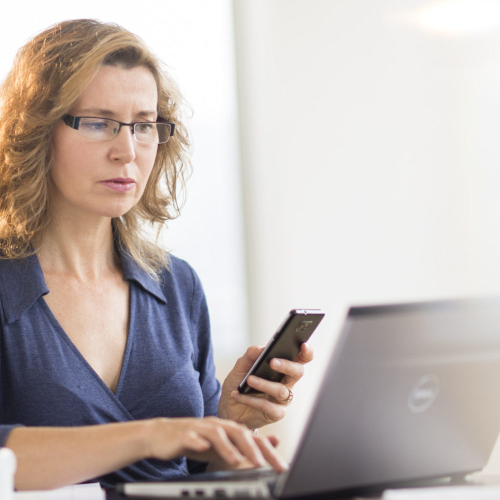 Businesswoman using laptop and phone