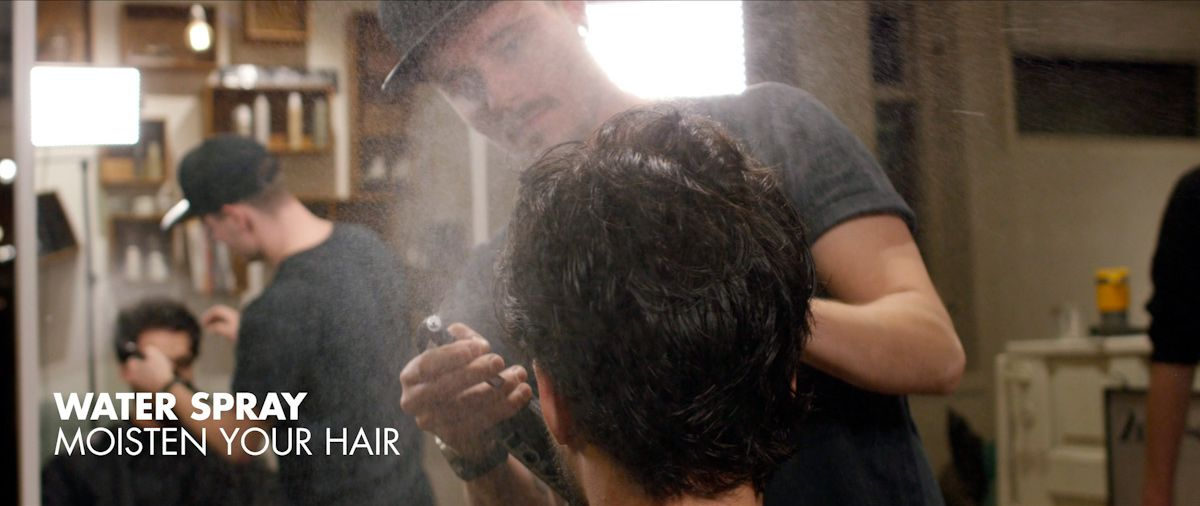 Moisten hair with water spray