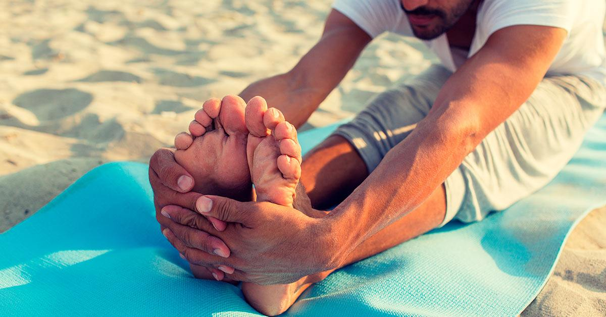 Man doing yoga on a mat in the sand
