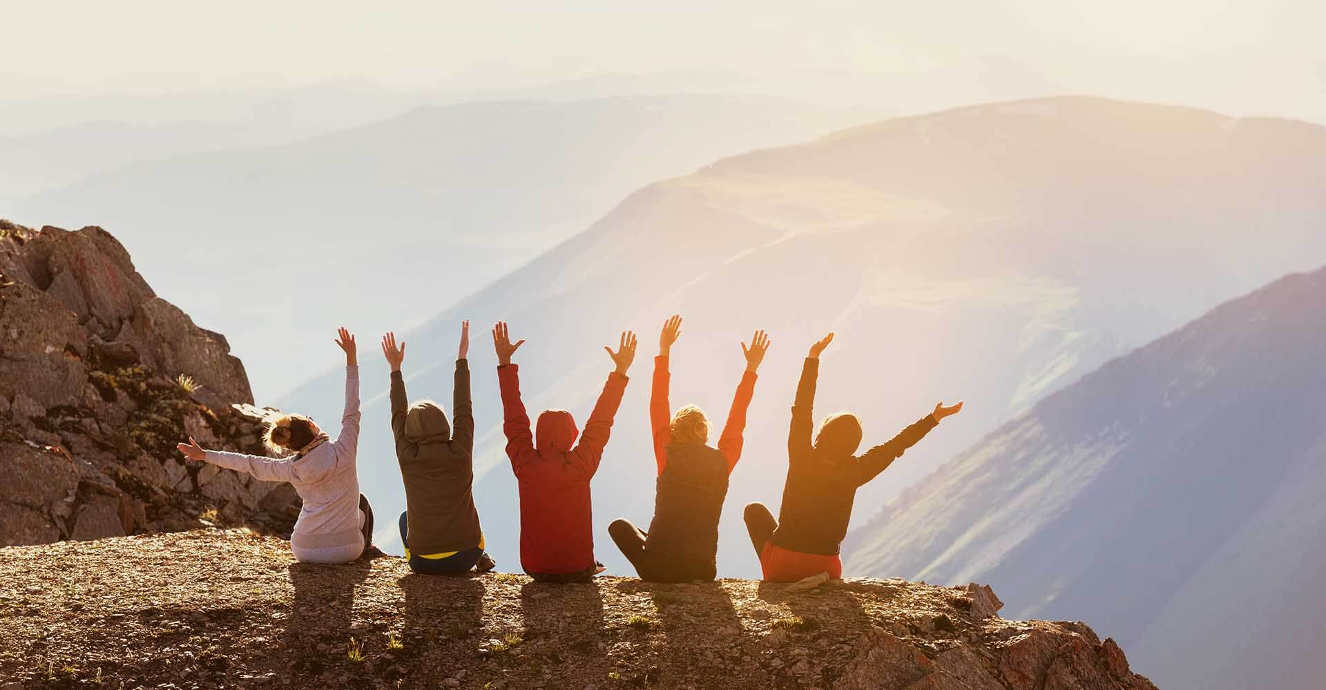 Group of five happy friends sittting at mountain top and waving their hands