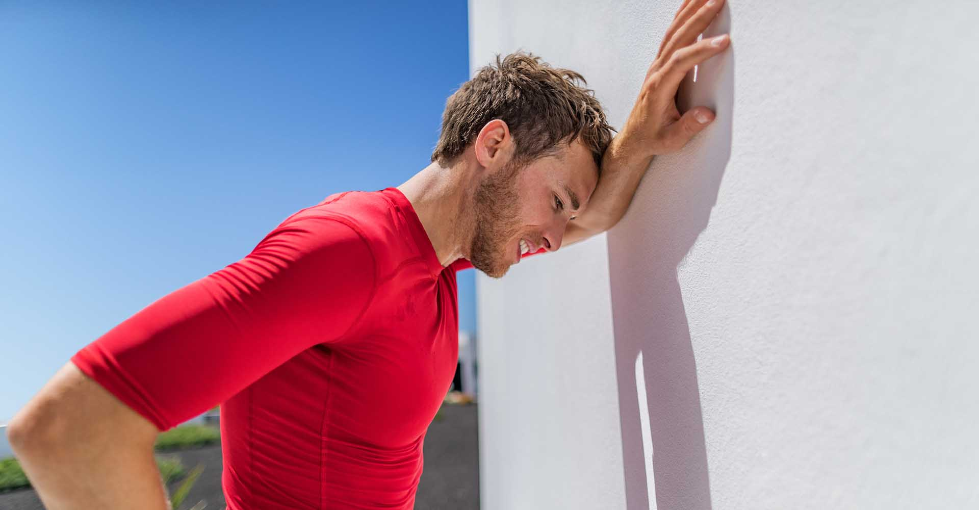Exhausted man leaning on the wall due to fatigue breathing difficulty after doing physical exercises