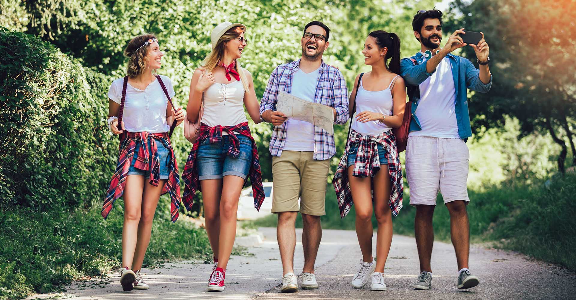 Group of five hapy friend walking with backpacks in woods