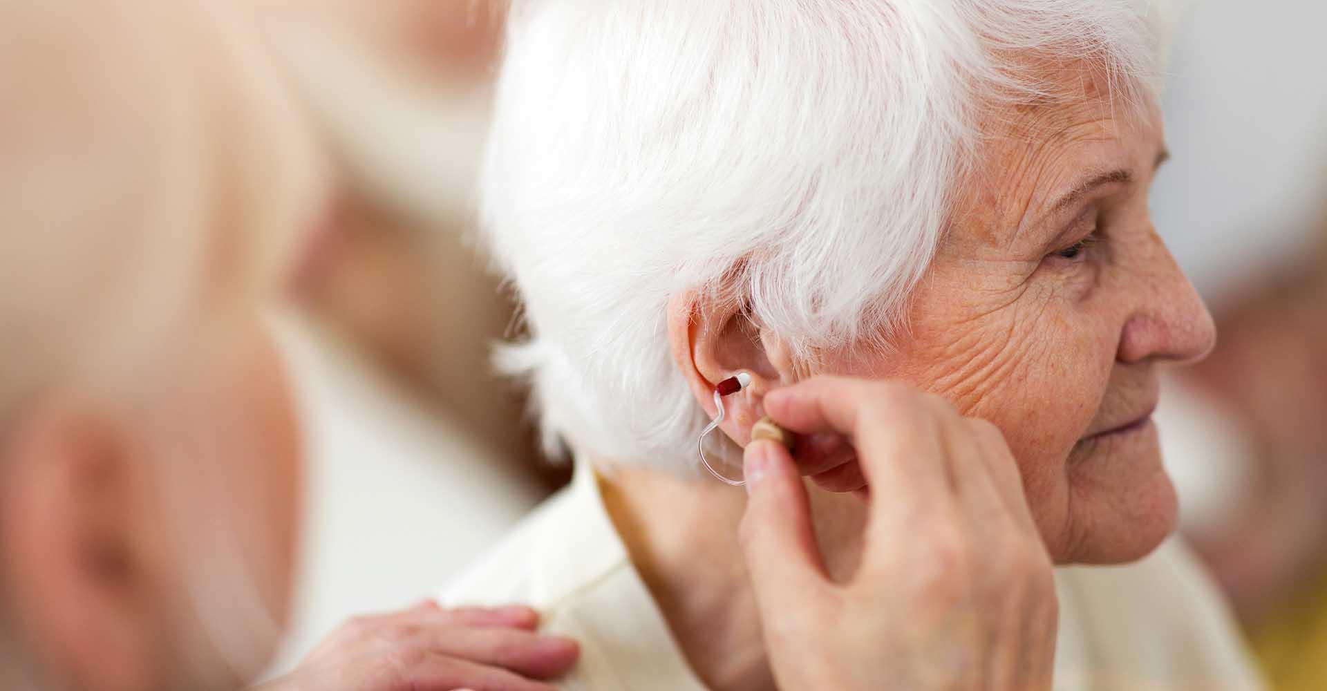 Female doctor applying hearing aid to senior woman's ear