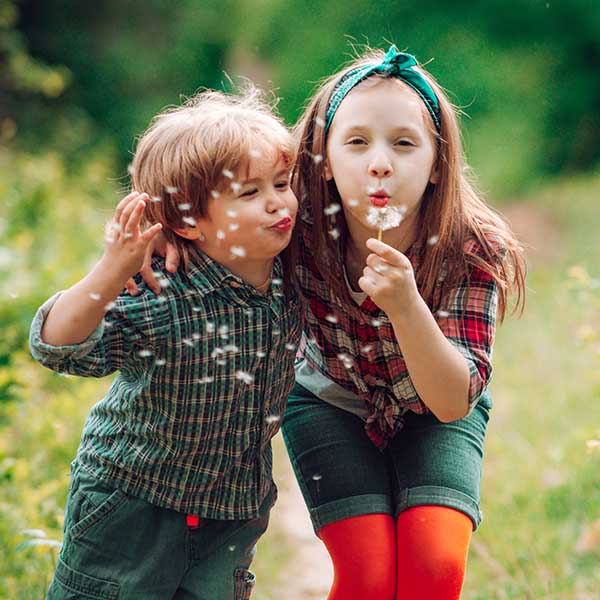 little boy and a girl blowing dandelion while playing in the garden