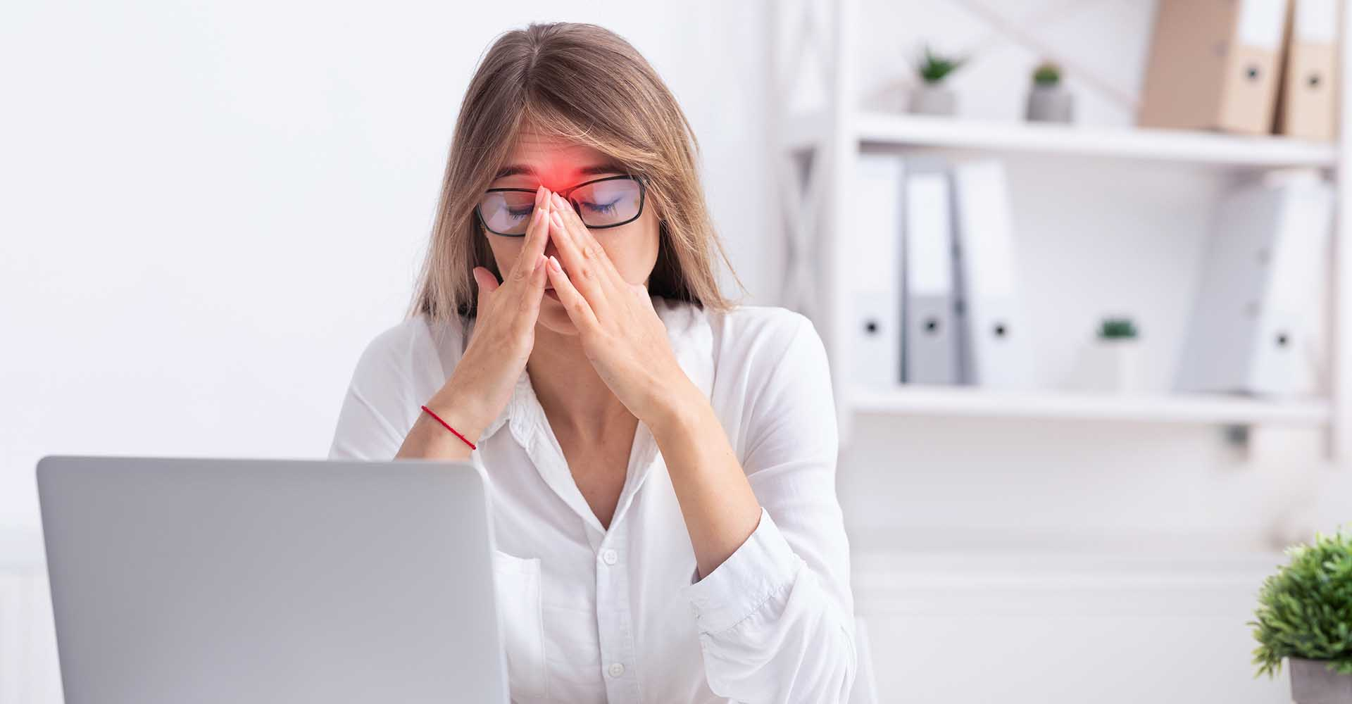 Businesswoman at work suffering srom sinus pain touching her nose and with both hands