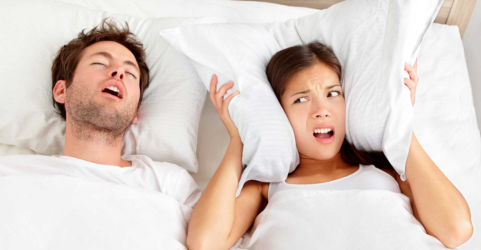 Upset woman covering her ears with a pillow who cannot sleep because of her husband's snoring