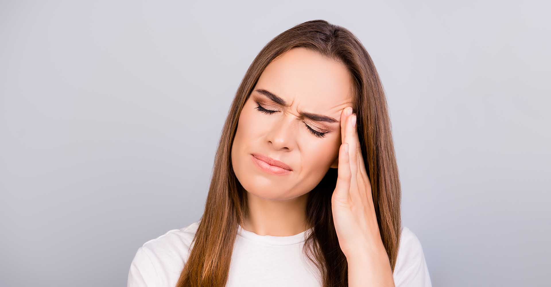 Beautiful woman suffering from strong migraine pressing her temple with her fingers