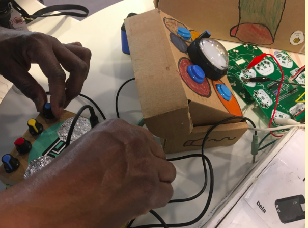 This image shows two hands assembling a musical device