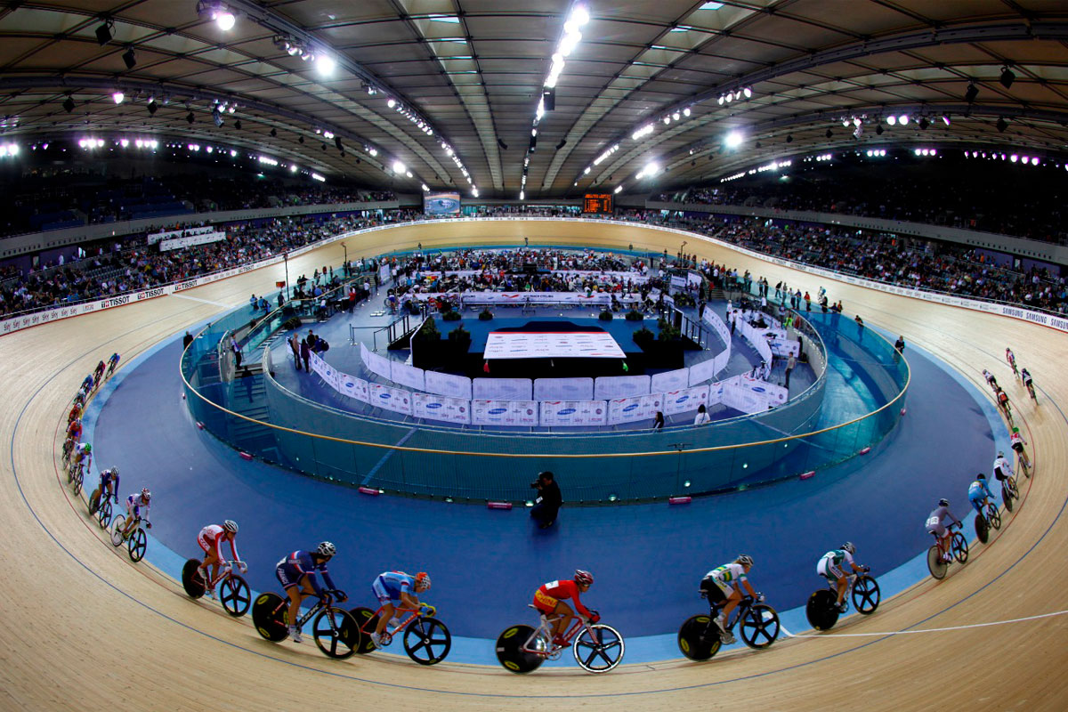 A wide-angled photograph showing riders cycling round one end of the track at Manchester's National Cycling Centre during the British Cycling National Track Championships 2017