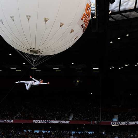 A photo of an aerial performer suspended from a large floating balloon at Old Trafford football stadium, Manchester, prior to the Rugby League Super League Final 2012
