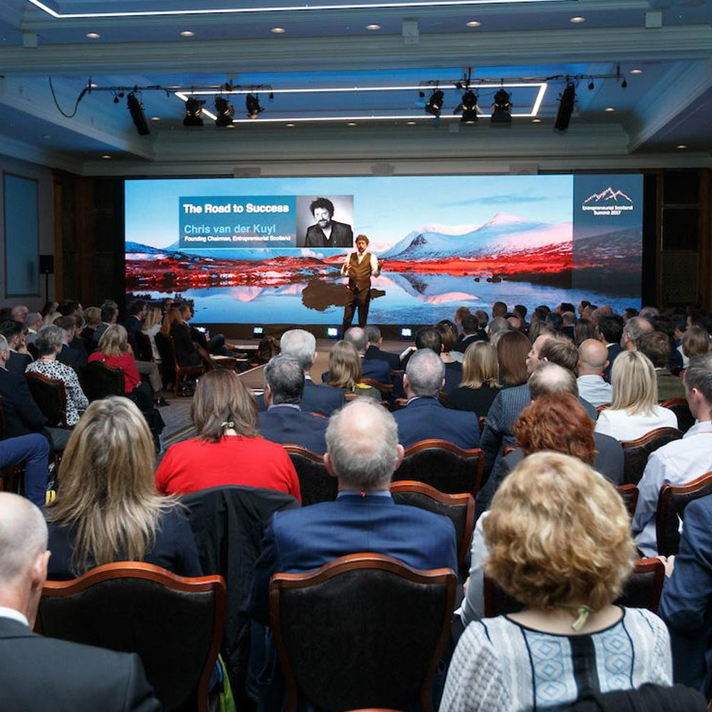 A photo of Chris van der Kuyt onstage addressing an audience at the Entrepreneurial Scotland Summit 2018 at Gleneagles Resort