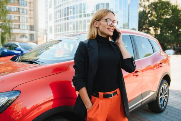Professional female manager standing near car at office building