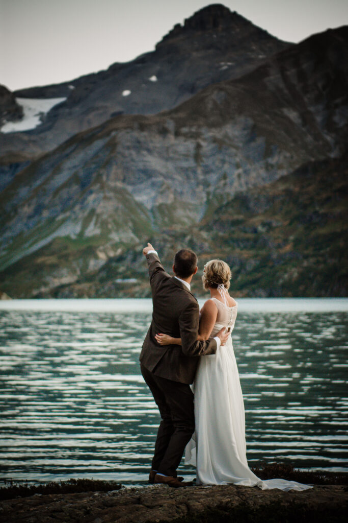 bridal couple from beyind, next to an alpine lake in the swiss mountains.
