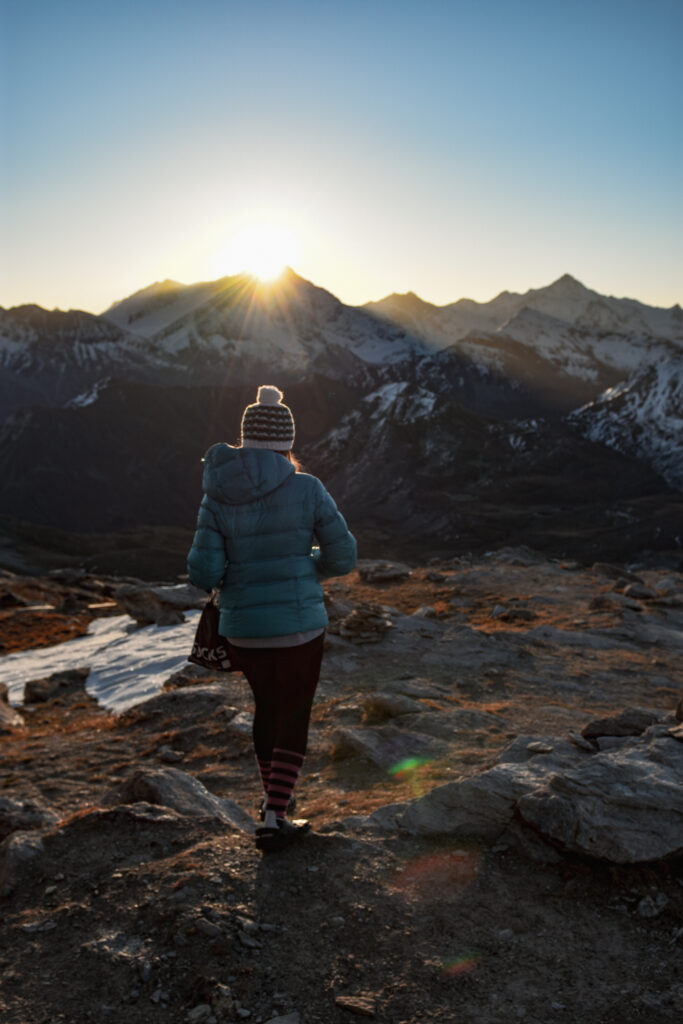 Woman wakling on a mountain ridge with the sun rising beyind the mountains in the background