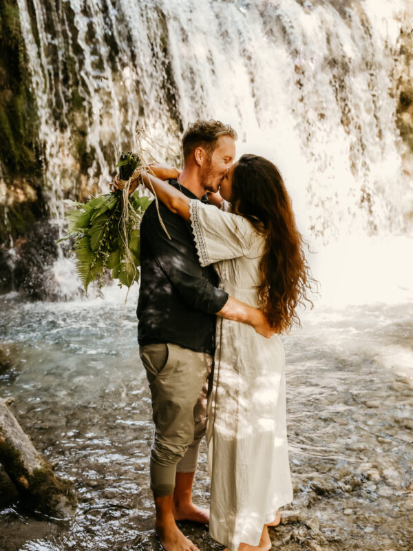 couple kissing in front of a waterfall during their elopement