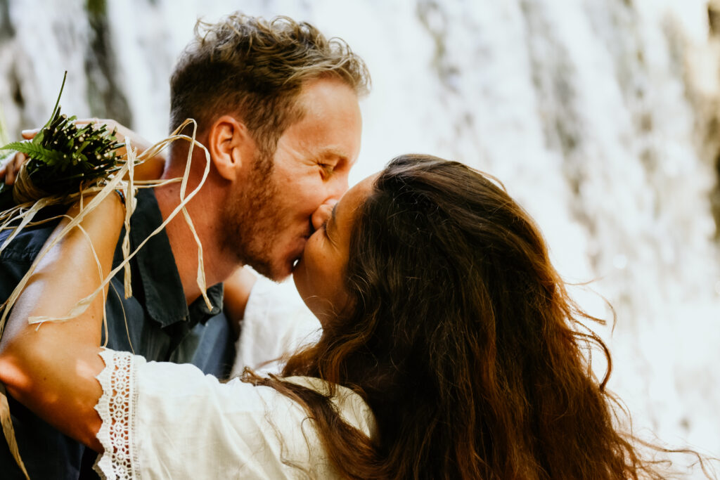 couple in love kissing in front of a waterfall in switzerland during their boho elopement.