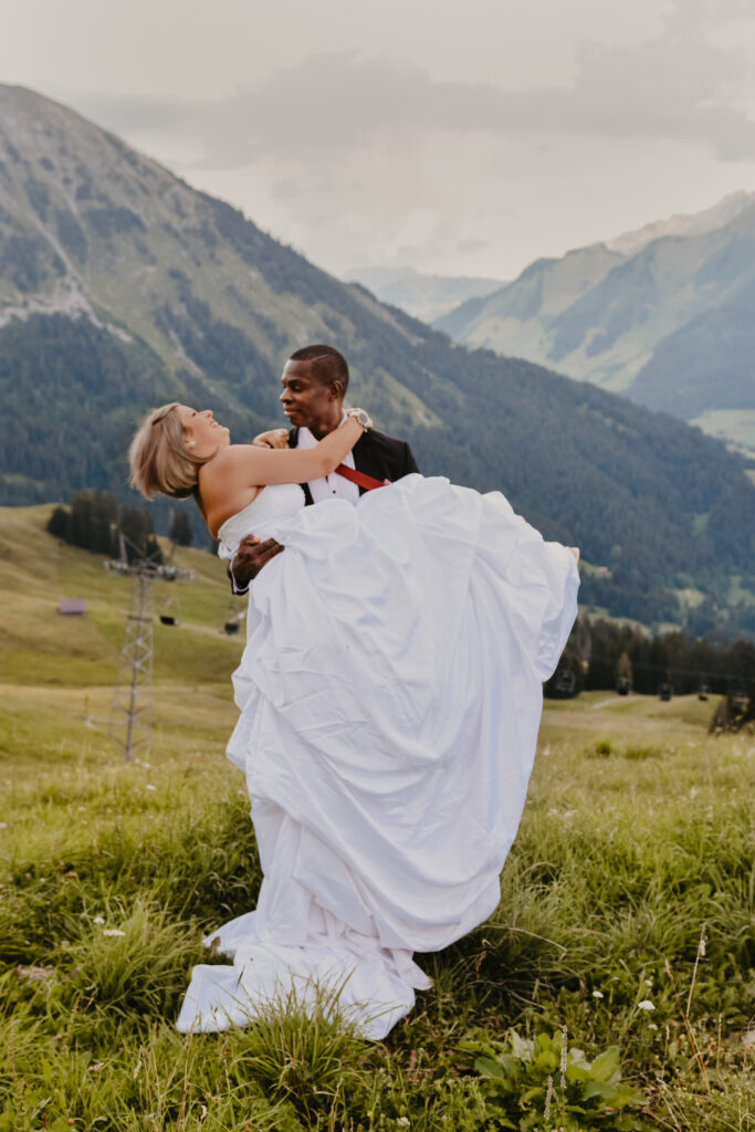 bi-racial couple on their elopement day in the mountains. groon holding his bride in his arms. Elopement in switzerland