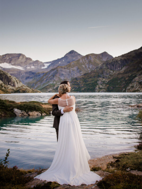 couple eloping in front of an alpine lake in switzerland at surnise