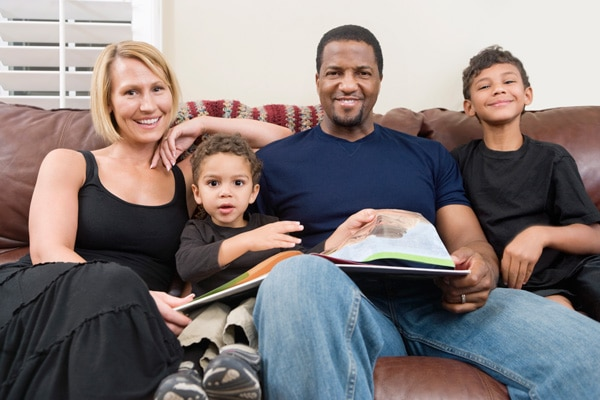 Image of a happy family sitting on a sofa discussing their Funeral Plans in York for CJS Legal Services Ltd