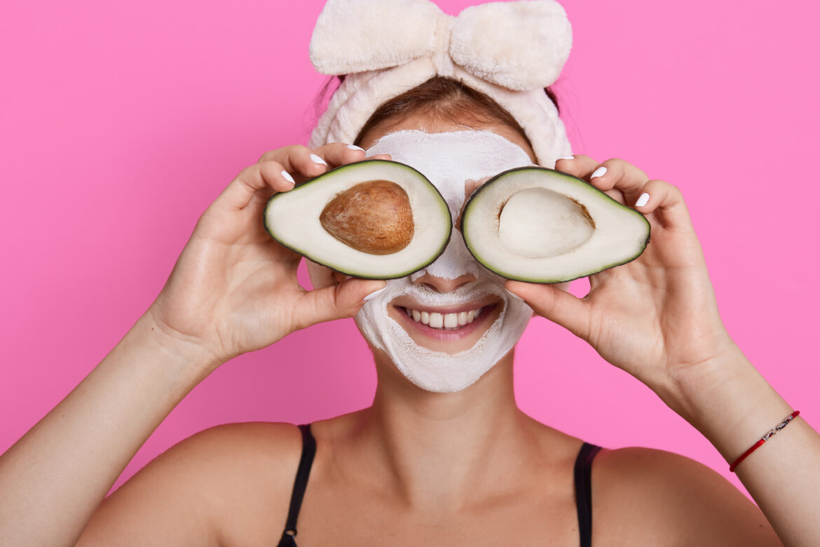 Closeup portrait of woman 20s with perfect skin holding avocado against her eyes isolated over pink background, healthcare, cosmetic procedures at home.
