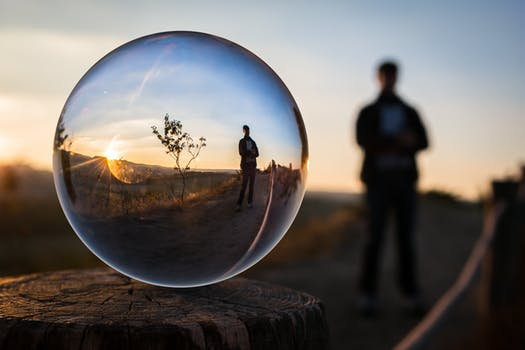 man standing near floating bubble containing his reflection