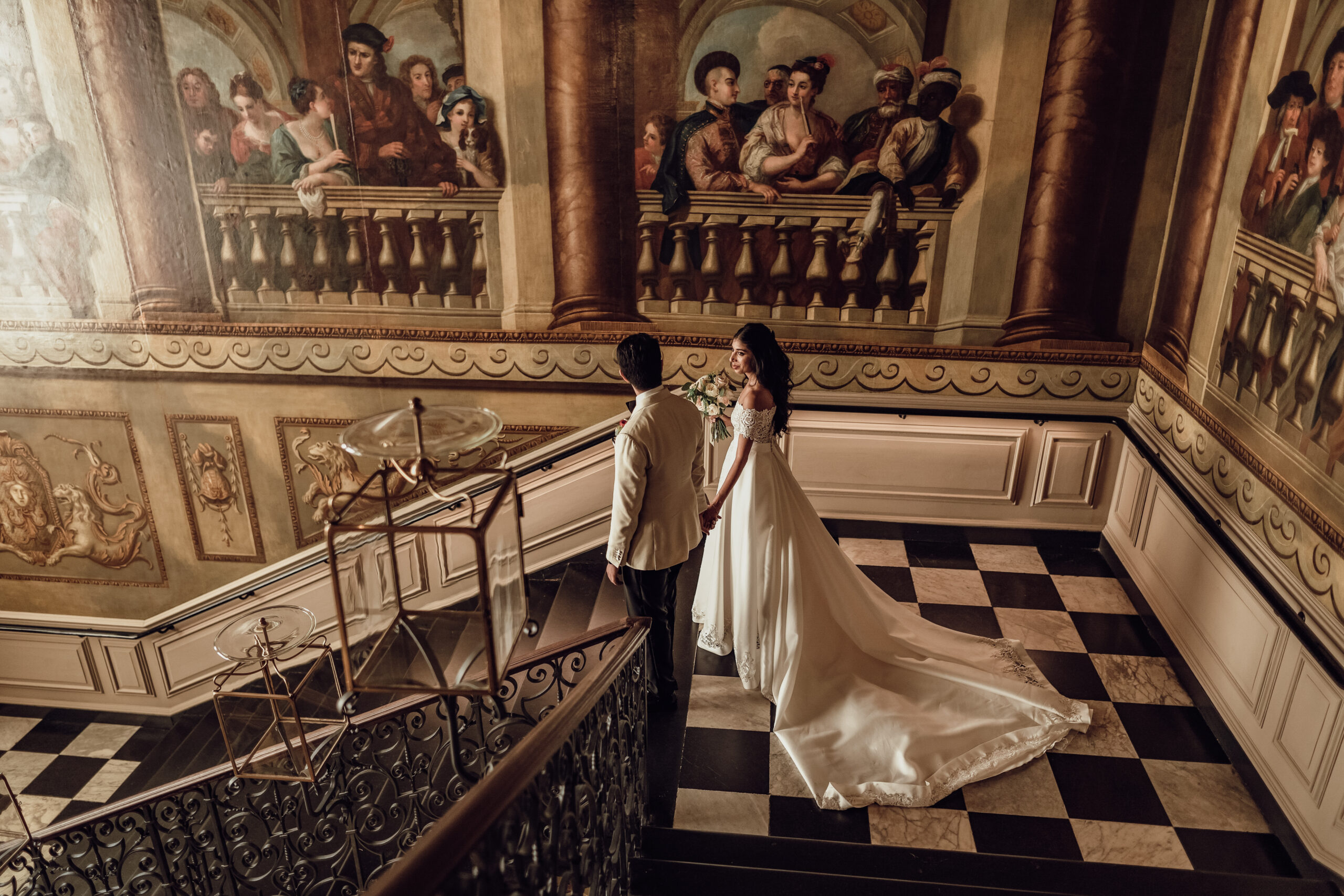 Wedding Couple walk down the ornate steps at Kensington Palace, bride wears a Valentine Wedding dress with a large train