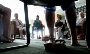 Low angle picture of a group sitting in chairs meditating