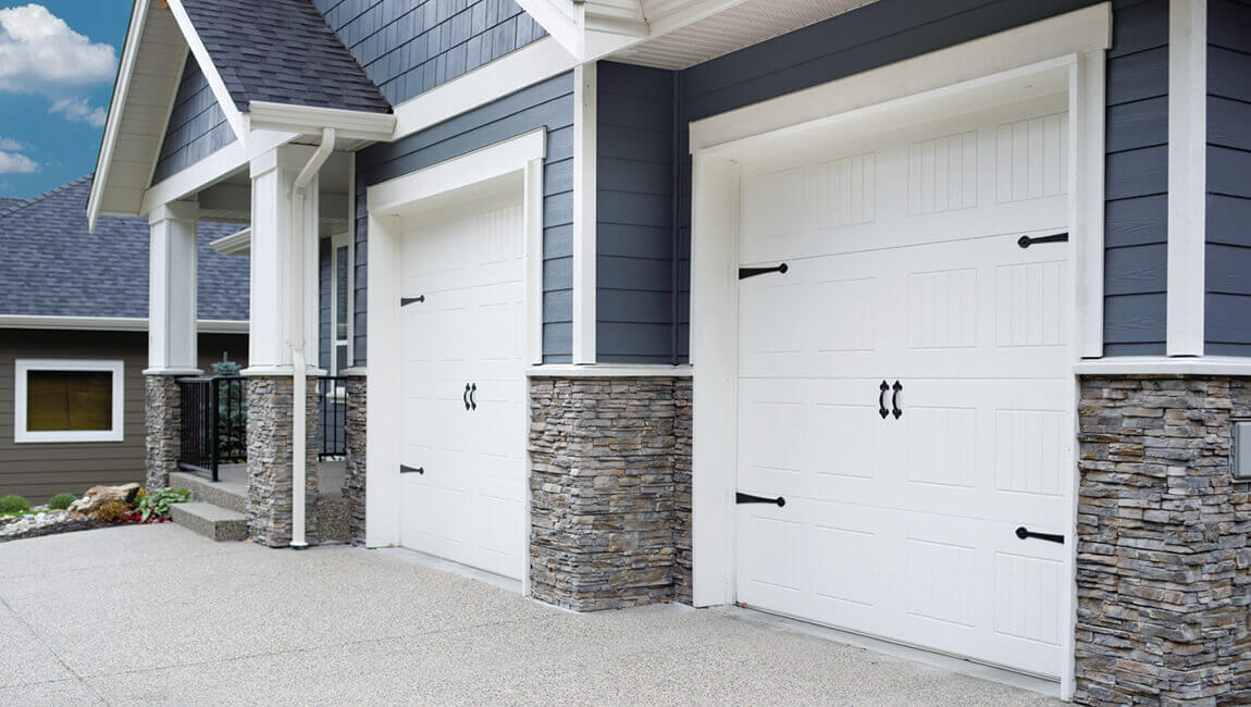 White steel craft carriage garage doors in a blue and brick sided double garage.
