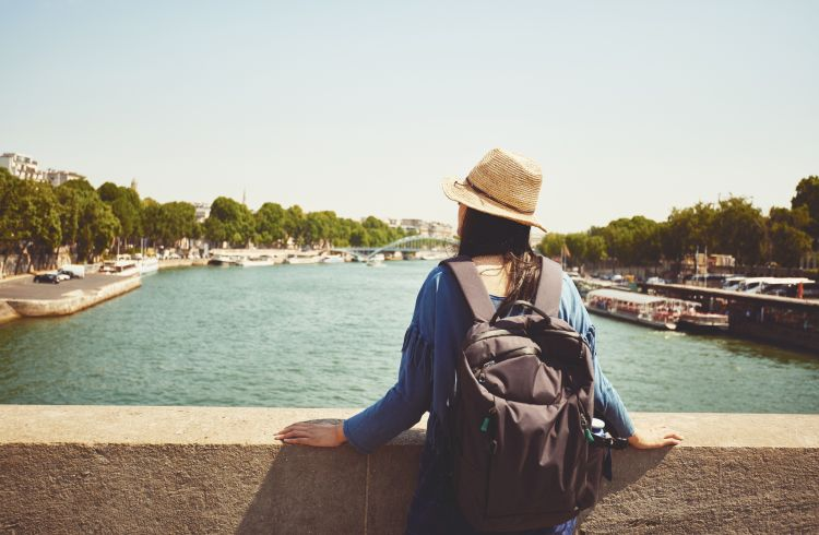a female tourist looking at the Seine in Paris