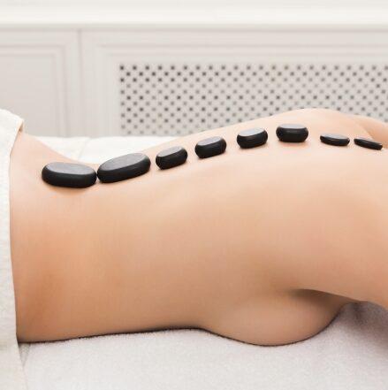 woman-getting-hot-stones-massage-at-spa-salon-5AVNW2T-679x442