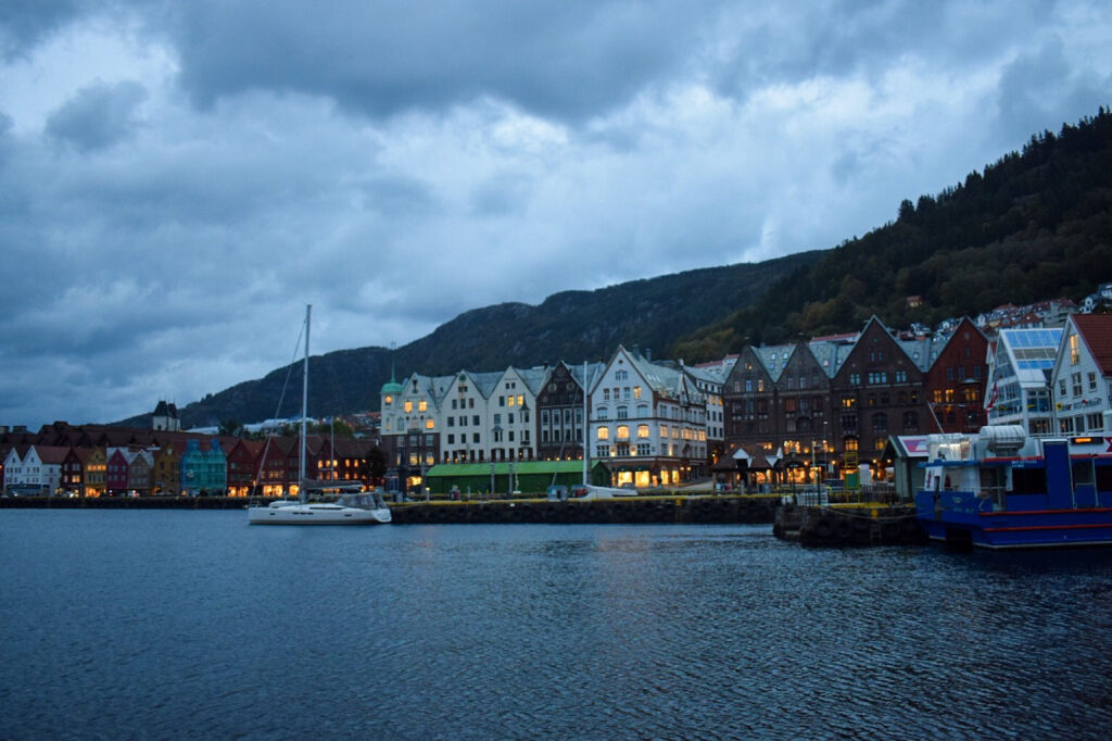 Old wooden houses of Bryggen by the fjord on a stormy evening in Bergen.